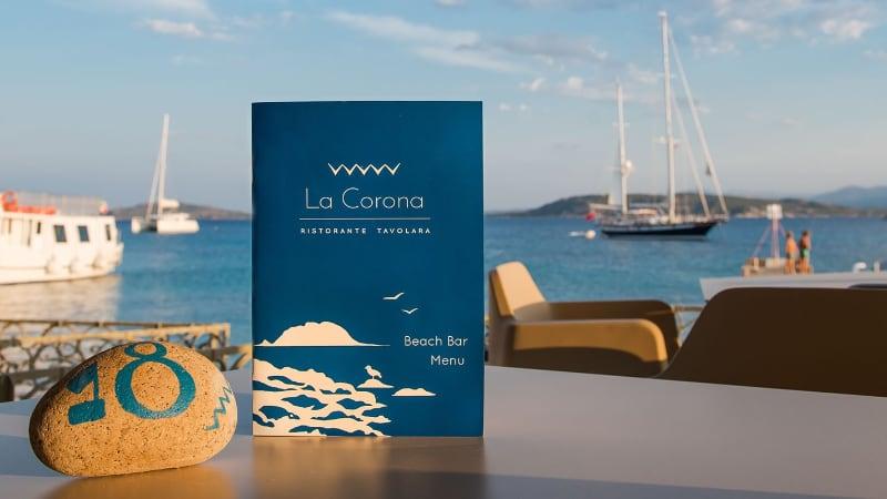 menu su un tavolo in riva al mare del Ristorante La Corona a Tavolara